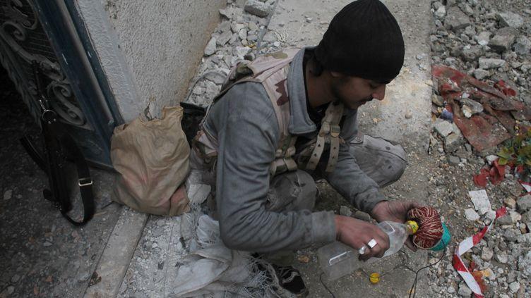Un combattant prépare une boule de feu, à Deir Ezzor,dans le nord de la Syrie, le 10 janvier 2014. (AHMAD ABOUD / AFP)