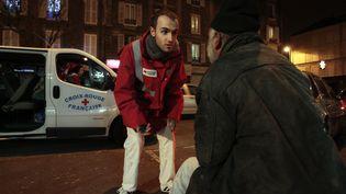 Un bénévole de la Croix-Rouge prend des nouvelles d'un SDF, à Joinville-le-Pont (Val-de-Marne) (FRANCOIS GUILLOT / AFP)