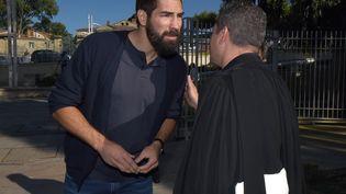 Le handballeur international Nikola Karabatic s'entretient avec son avocat Michael Corbier, lundi 22 juin 2015 à Montpellier (Hérault). (PASCAL GUYOT / AFP)