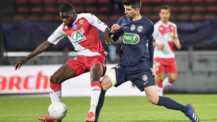 Le défenseur de Monaco Djibril Sidibe (à gauche)etle milieu de terrain de Rumilly Vallieres Mathieu Guillaud (à droite) pendant lademi-finale de Coupe de France au stade du Parc des Sports à Annecy, le 13 mai 2021. (PHILIPPE DESMAZES / AFP)