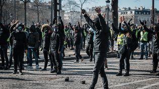 Des manifestantscagoulés à Paris, sur les Champs-Elysées, le 16 mars 2019. (KARINE PIERRE / HANS LUCAS / AFP)