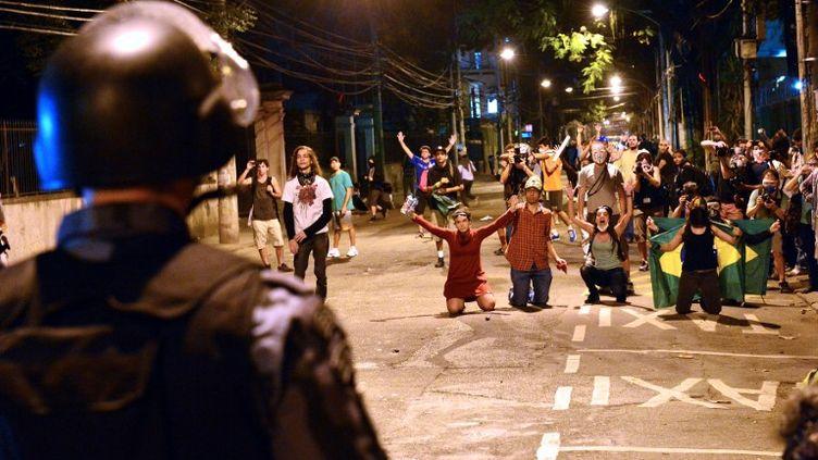 Des manifestants font face à la police, dimanche 30 juin 2013 dans les rues de Rio de Janeiro (Brésil). (YASUYOSHI CHIBA / AFP)