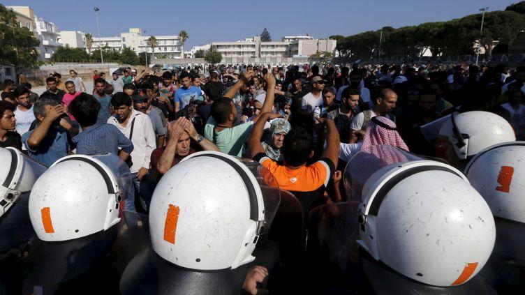 (Les policiers anti-émeutes grecs ont tenté de maintenir les migrants dans le stade de football de la ville de Kos, en Grèce © REUTERS/ Yannis Behrakis)