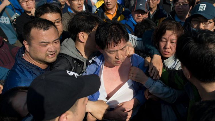 """Des proches de victimes du naufrage du """"Sewol"""", en Corée du Sud, molestentun responsable des garde-côtes, le 24 avril 2014, à Jindo. (ED JONES / AFP)"""