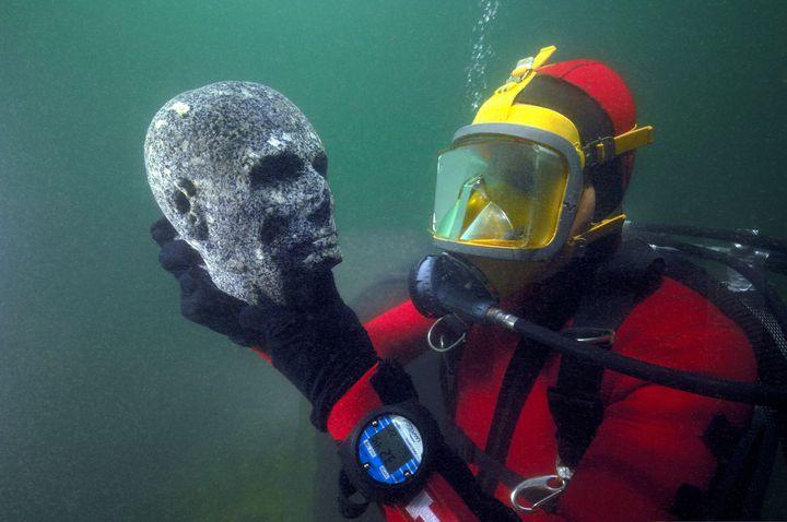 Un plongeur remonte une tête de prêtre de l'époque ptolémaïque en granite noir dans le port oriental d'Alexandrie  (Christoph Gerigk © Franck Goddio / Hilti Foundation)