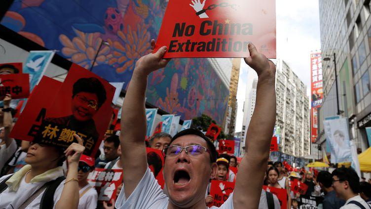 Des manifestants protestent contre un projet de loi d'extradition à Hong Kong, le 9 juin 2019. (THOMAS PETER / REUTERS)