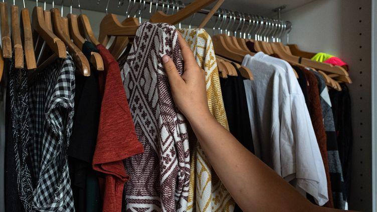 Une femme choisit dans sa garde-robe des vêtements à donner pour qu'ils soient recyclés. Versailles, septembre 2020 (KARINE P?RON LE OUAY / HANS LUCAS)