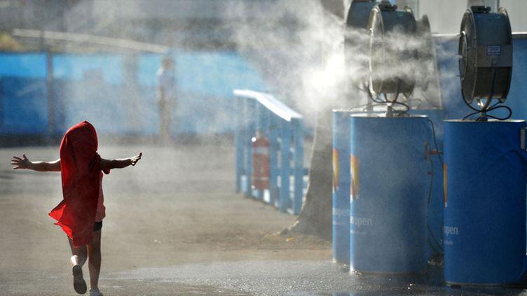 Une petite fille s'amuse avec des brumisateurs à Melbourne (Australie), le 15 janvier 2013. (PETER PARKS / AFP)