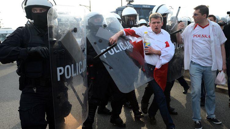 Des accrochages ont eu lieu mardi soir 12 juin entre supporteurs russes et polonais et la police a utilisé un canon à eau et des gaz lacrymogènes pour disperser des hooligans polonais à Varsovie. (DIMITAR DILKOFF / AFP)