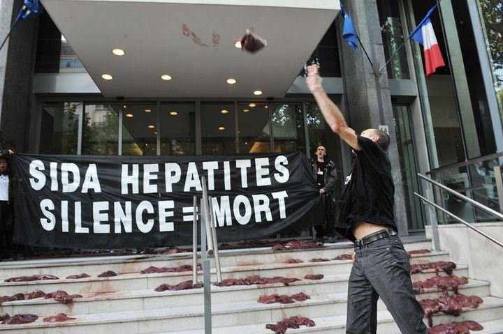 Des militants d'Act Up jettent des foies d'animaux devant le ministère de la Santé, le 19 mai 2010, pour protester contre la politique française concernant le sida et les hépatites. (BERTRAND LANGLOIS / AFP)