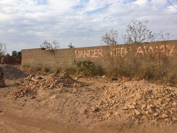 """""""Danger, éloignez-vous!"""" Cetavertissement (en anglais), écrit sur un mur près de l'ancienne mine de plomb,tente de dissuader les habitants de Kabwe d'y entrer. (Juliane Kippenberg / Human Rights Watch 2018)"""