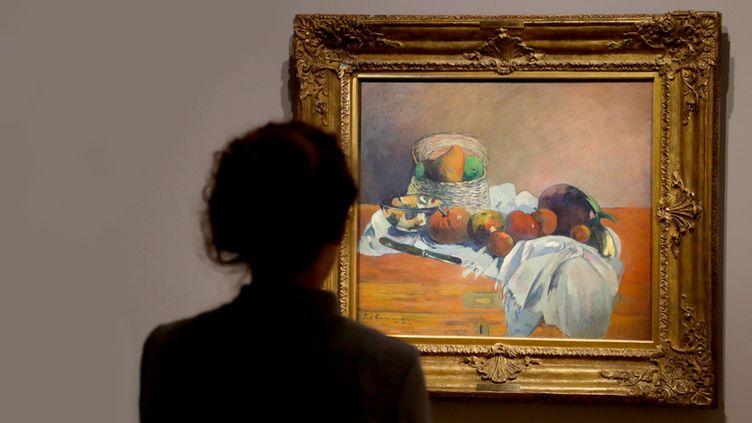 """Une visiteuse observe un précieux tableau de la collection Emil Bührle : """"Nature morte au couteau"""" de Paul Gauguin (1901), au Musée Maillol à Paris (18 mars 2019)  (François Guillot / AFP)"""