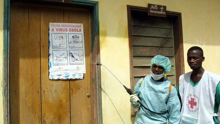 Deux membres de la Croix-Rouge en charge de la désinfection de l'hôpital de Kelle (République démocratique du Congo), le 9 mars 2003. (DESIREY MINKOH / AFP)