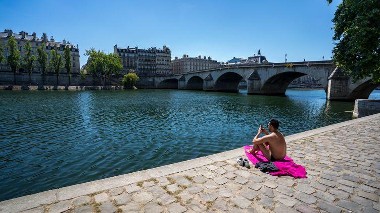 Un homme prend le soleil sur les quais de Seine à Paris, le 24 juin 2020. (GABRIELLE CEZARD / HANS LUCAS / AFP)