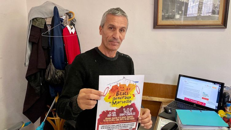 Fathi Bouaroua, responsable d'Emmaüs Pointe-Rouge à Marseille, montre les affiches à l'origine du litige avec la mairie, le 5 décembre 2019. (DAVID AUSSILLOU / RADIO FRANCE)