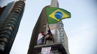 Un manifestant avec le drapeau brésilien lors du rassemblement à Belo Horizonte, Brésil, le 20 juin 2013. Les manifestations qui secouent le pays en ce moment sont le révélateur d'un malaise plus profond dans un pays qui connaît actuellement une croissance est en berne et une poussée de l'inflation. (YURI CORTEZ / AFP)
