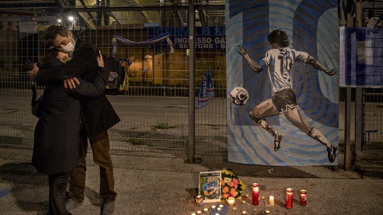 A Naples, deux personnes s'étreignent dans un hommage rendu à Diego Maradona, décédé le 25 novembre, à 60 ans (ALESSIO PADUANO / ANADOLU AGENCY)