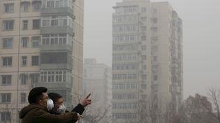 Deux hommes bravent le nuage de pollution à Pékin (Chine), le 25 décembre 2015. (KIM KYUNG HOON / REUTERS)