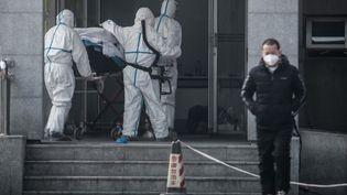 Le personnel hospitalier de l'hôpital de Jinyintan, à Wuhan en Chine, transportant un patient atteint du mystérieux virus similaire au Sras, le 18 janvier 2020. (STR / AFP)