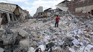 Un homme sur les décombres d'immeubles effondrés, le 20 avril 2016, après le séisme qui a fait au moins 602 morts, en Equateur. (JUAN CEVALLOS / AFP)