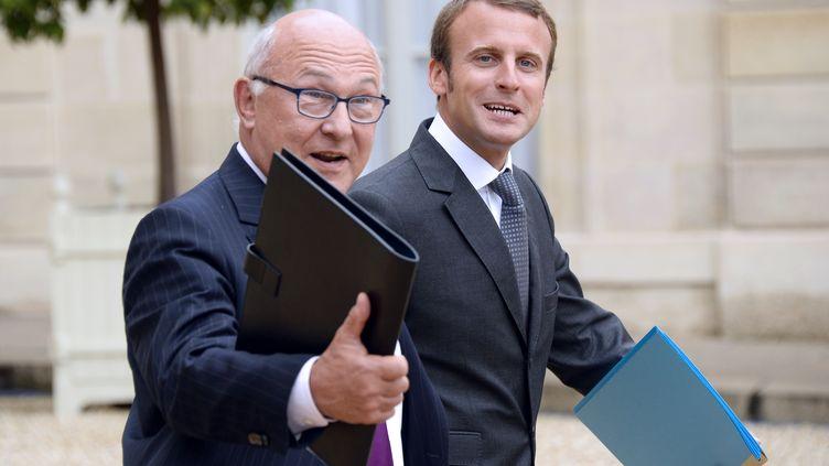 Les ministres des Finances, Michel Sapin (G), et de l'Economie, Emmanuel Macron, quittent l'Elysée après le Conseil des ministres, le 27 août 2014. (BERTRAND GUAY / AFP)