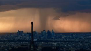 Une photo prise de l'observatoire de la Tour Montparnasse à Paris montre la tour Eiffel et le quartier de la Défense sous un large nuage de pluie, le mercredi 30 mai 2018. (PHILIPPE LOPEZ / AFP)