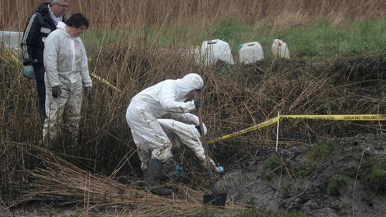 Des officiers de police procèdent aux fouilles des environs de la maison d'Hubert Caouissin, le 9 mars 2017 àPont-de-Buis (Finistère). (FRED TANNEAU / AFP)