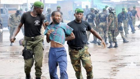 Un manifestant de l'opposition emmené par les forces de sécurité dans le stade de Conakry, le 28 septembre 2009. (Photo/AFP)