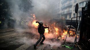 """Un manifestant lance un projectile en direction des forces de l'ordre, lors d'un rassemblement des """"gilets jaunes"""", le 1er décembre 2018 à Paris. (ABDULMONAM EASSA / AFP)"""