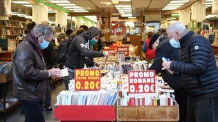 Des clients d'une librairie en train de choisir des livres, le 28 novembre 2020, à Paris. (ALAIN JOCARD / AFP)