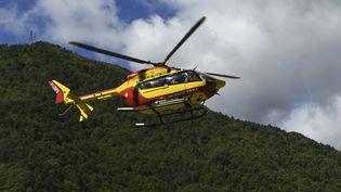 Un hélicoptère de la sécurité civile transporte une personne blessée, le 3 octobre 2020, depuis Roquebillière (Alpes-Maritimes). (NICOLAS TUCAT / AFP)