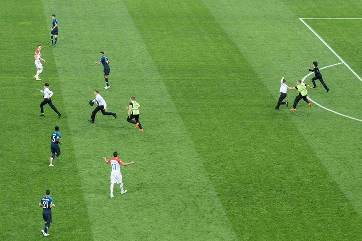 Des membres du groupe Pussy Riot courent sur la pelouse du stade Loujniki de Moscou (Russie), dimanche 15 juillet, lors de la finale de la Coupe du monde entre la France et la Croatie. (ELMAR KREMSER/ SVEN SIMON / AFP)