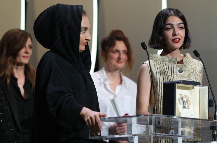 """L'actrice iranienne et fille de Jafar Panahi, Solmaz Panahi (à droite) accepte le Prix du scénario pour """"3 visages"""" à la place de son père, sous le regard de Chiara Mastroiani et d'Alice Rohrwacher, elle aussi lauréate de ce prix pour """"Heureux comme Lazzaro"""".  (Valery HACHE / AFP)"""