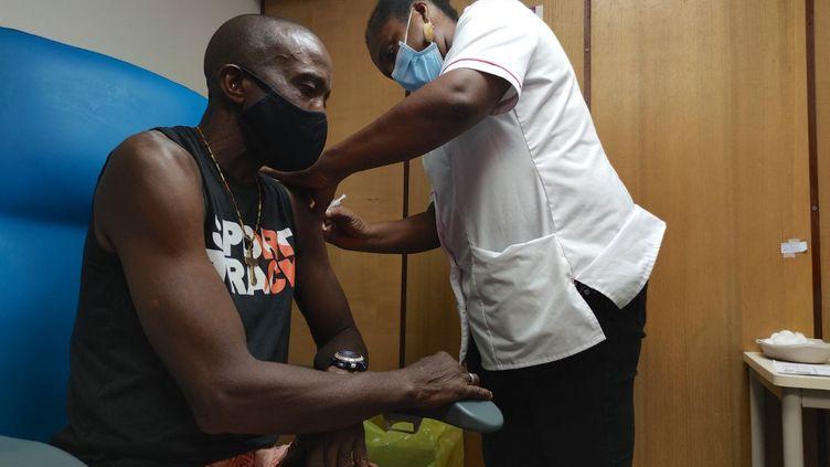 Un homme reçoit une dose du vaccin Pfizer-BioNTech contre le Covid-19, le 6 août 2021 à Pointe-à-Pitre, en Guadeloupe. (CEDRICK ISHAM CALVADOS / AFP)