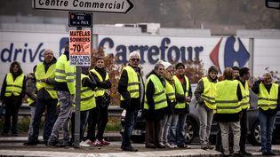 """Des """"gilets jaunes"""" manifestent devant un magasin Carrefour à Givors (Rhône), le 17 novembre 2018. (JEAN-PHILIPPE KSIAZEK / AFP)"""