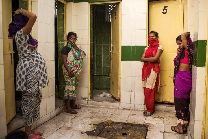 En Inde, les installations collectives sont une réponse à la pénurie de toilettes, mais sans système organisé pour le nettoyage et l'entretien, la défécation reste un problème de santé publique. Ici, des femmes attendent l'ouverture de la seule cabine en état de marche à New Delhi. (ANDREA BRUCE/ NOOR POUR NATIONAL GEOGRAPHIC MAGAZINE)