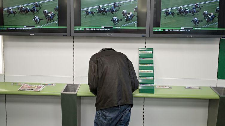 Un joueur dans une boutique PMU City, à Lyon (Rhône) le 5 janvier 2012.  (JEAN-PHILIPPE KSIAZEK / AFP)