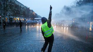 """Un """"gilet jaune"""" devant les forces de l'ordre lors de """"l'acte5"""" du mouvement sur les Champs-Elysées, à Paris, le 15décembre2018. (ZAKARIA ABDELKAFI / AFP)"""