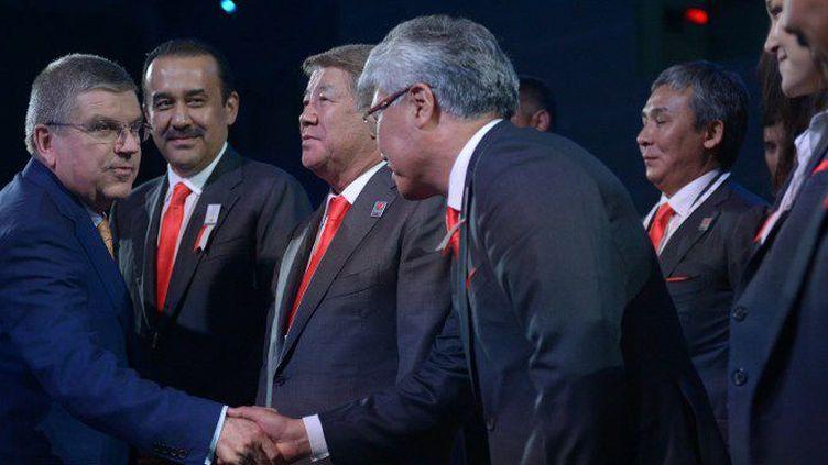 Le président du Comité international olympique Thomas Bach serre la main aux membres de la délégation kazakhstanaise après l'annonce de la victoire de Pékin. (MOHD RASFAN / POOL / AFP)