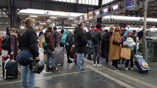 Jour de grand départ à la gare de l'Est, à Paris, les passagers d'un TGV OUIGO font la queue pour passer un portique de sécurité avant d'embarquer, le 19 décembre 2020. (AMAURY CORNU / HANS LUCAS)