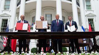 Le ministre des Affaires étrangères Abdullatif Al-Zayani de Bahrein, le Premier ministre israélien, Benyamin Nétanyahou, le président américain, Donald Trump, et le ministre des Affaires étrangères des Emirats arabes unis, Abdullah Ben Zayd Al-Nahyan, montrant l'accord signé entre les trois pays, le 15 septembre 2020. (SAUL LOEB / AFP)
