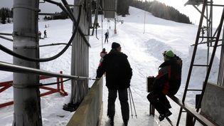 Des vacanciers empruntent les remontées mécaniques dans la station de ski d'Autrans (Isère) le 30 décembre 2008. (FRED DUFOUR / AFP)