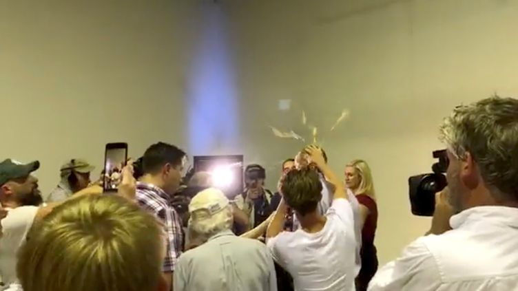 Un jeune homme écrase un œuf sur la tête du sénateur australien d'extrême droite Fraser Anning, le 16 mars 2019, à Melbourne (Australie). (SOCIAL MEDIA / REUTERS)