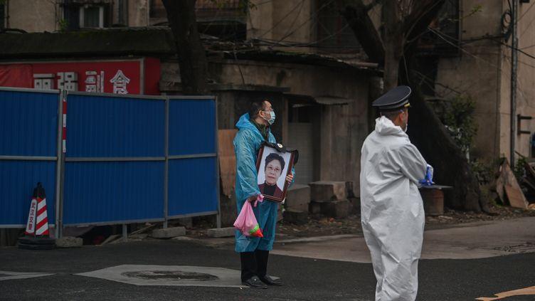 Un homme tient un portrait d'une proche défunte devant un cimetière de Wuhan, le 31 mars 2020, peu après que les habitants ont commencé à récupérer les cendres des personnes mortes lors de la période de confinement. (HECTOR RETAMAL / AFP)