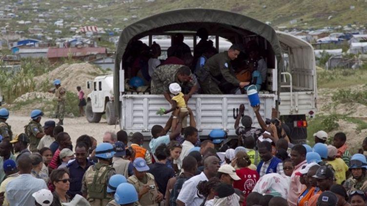 Des casques bleus de l'Onu aident la population à déménager, le 4 novembre 2010 à Port-au-Prince. (AFP - Minustah)