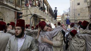 Des juifs ultra-orthodoxes en costume célèbrent la fête de Pourim dans le quartier ultra-orthodoxe de Méa Shéarim, à Jérusalem, le 11 mars 2020. (MENAHEM KAHANA / AFP)