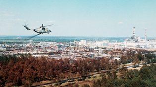 Un hélicoptère militairediffuse un produit supposé réduire la contamination de l'air,au-dessusde lacentralenucléaire de Tchernobyl, à Prypiat, en URSS (aujourd'hui sur le territoire ukrainien), quelques jours après la catastrophe du 26 avril 1986. (STF / TASS / AFP)
