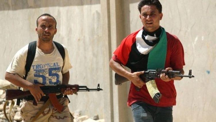 Deux rebelles patrouillent dans les rues de Zaouïah. (MARC HOFER / AFP)