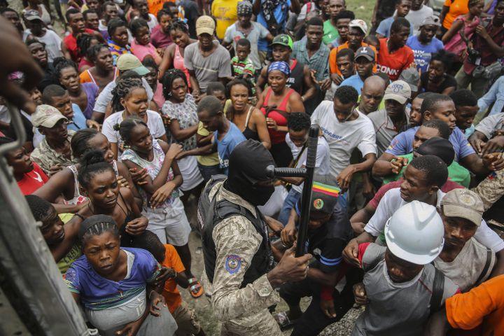 Un officier de police fait respecter l'ordre pendant une distribution de riz aux Cayes (Haïti), lundi 16 août 2021. (JOSEPH ODELYN / AP / SIPA)