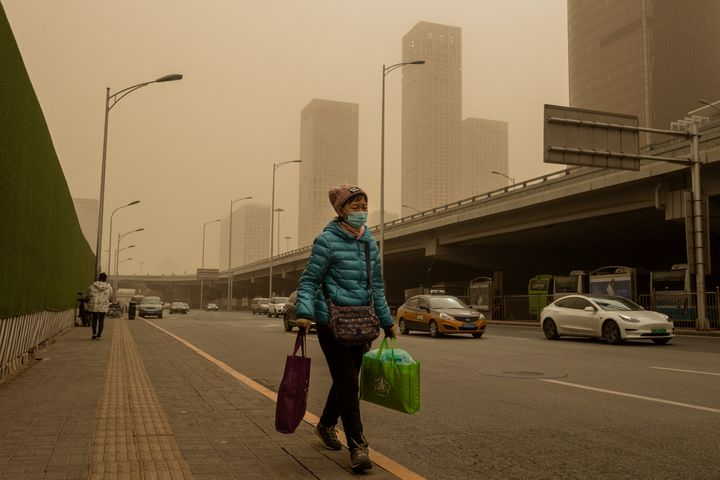 Une passante dans une rue de Pékin, le 15 mars 2021. (NICOLAS ASFOURI / AFP)
